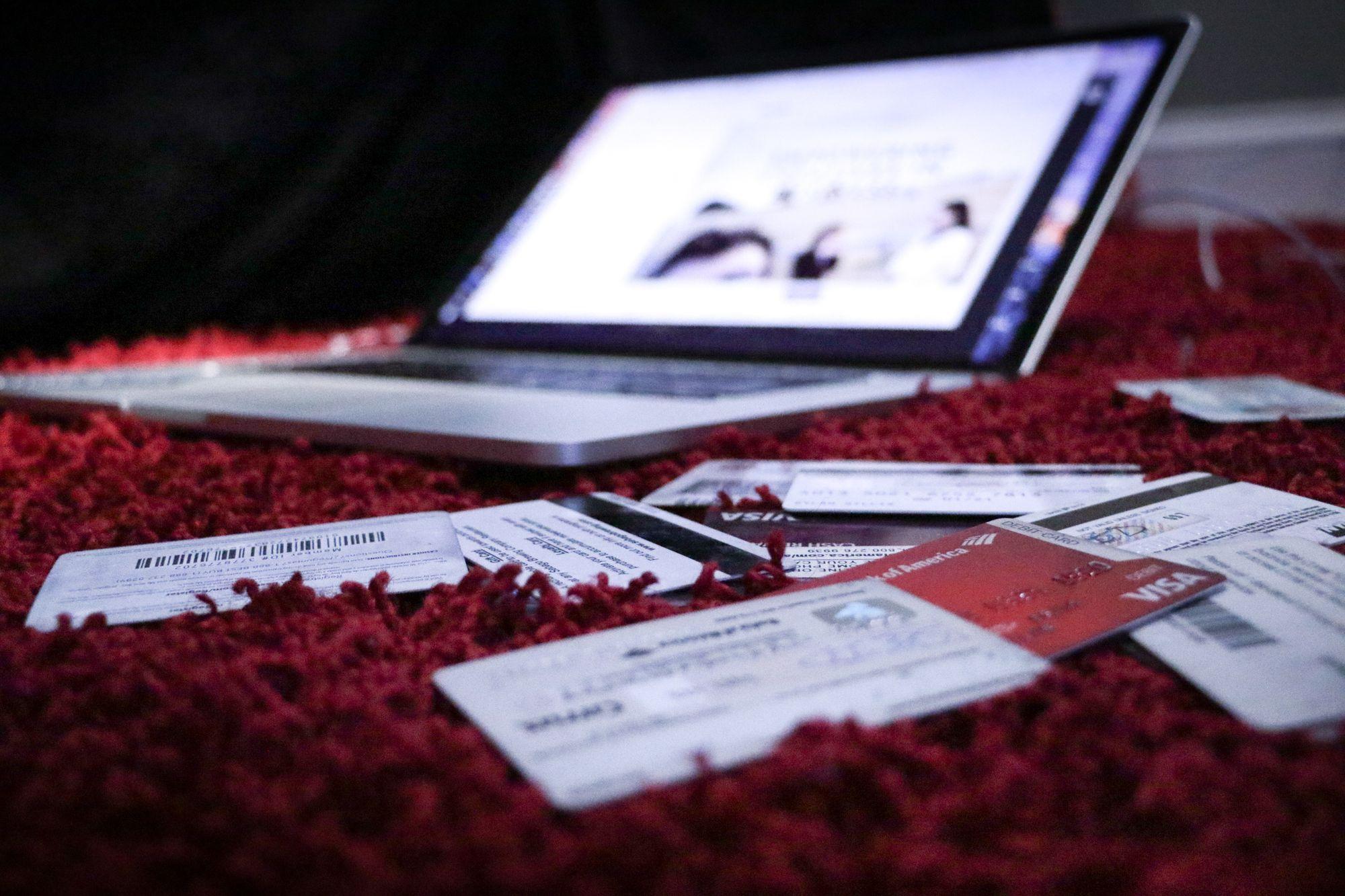 ordinateur portable posé sur un tapis et entouré de plusieurs carte de crédit et de fidélité - blog.troov.com